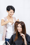 Hair stylist cuts hair of woman in hairdress salon Royalty Free Stock Image