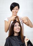 Hair stylist cuts hair of woman in hairdressing salon Royalty Free Stock Image