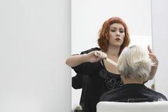 Hair Stylist Cutting Senior Woman's Hair Royalty Free Stock Photo