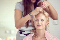 Hair stylist designer making hairstyle for woman royalty free stock photography
