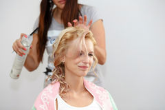 Hair stylist designer making hairstyle for woman Stock Images