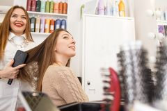 Hair stylist drying hair for female client. Beautifying concept Royalty Free Stock Image
