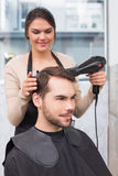 Hair stylist drying mans hair Royalty Free Stock Image