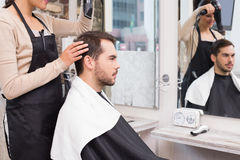 Hair stylist drying mans hair Royalty Free Stock Images