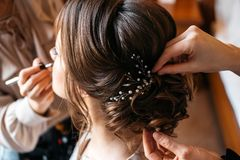 A hair stylist and make-up artist prepare a bride for the wedding day. Cropped image stock photography