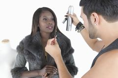 Hair Stylist Makes Adjustments To Model In Fur Jacket. Hair stylist makes adjustments to happy African American model in fur jacket Royalty Free Stock Photo