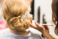 Hair stylist makes the bride before a wedding. Hair stylist makes the bride before the wedding Royalty Free Stock Images