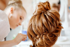 Hair stylist makes the bride before the wedding. Hair stylist makes the bride on the wedding day stock photography