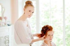 Hair stylist makes the bride on the wedding day Stock Photos