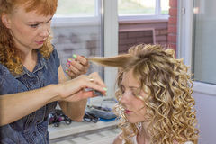 Hair stylist makes the bride before wedding Stock Photo