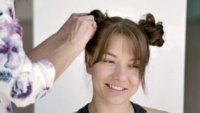 Hair stylist makes a young beautiful caucasian brunette`s hairstyle stock footage
