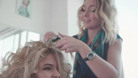 Hair stylist making curls on customer hair using electric curler. Stylist, Hairdresser is Making The Hairstyle, Fixing the Hairs. Woman with Long Brown Hairs stock video