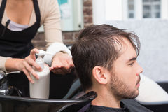 Hair stylist putting conditioner in mans hair. At the hair salon Royalty Free Stock Images