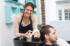 Hair stylist putting conditioner in mans hair Stock Photos