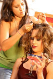 Hair Stylist on Set. Professional hair-stylist working on model during photo-shoot Stock Photography