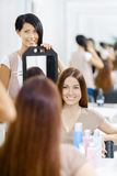 Hair stylist showing the hairstyle of client in mirror Stock Image