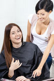 Hair stylist talking to the client sitting on chair Stock Image