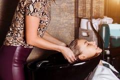 Beautiful woman washing hair in a hair salon stock photo