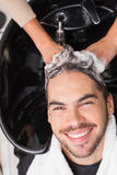 Hair stylist washing mans hair Stock Photography