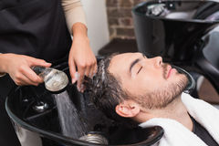 Hair stylist washing mans hair. At the hair salon Royalty Free Stock Photo