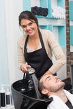 Hair stylist washing mans hair Royalty Free Stock Photography