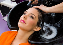 Hair stylist washing woman head Stock Images
