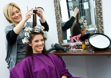 Hair stylist at work. Hair stylist work on woman hair in salon Royalty Free Stock Image