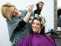 Hair stylist at work. Hair stylist work on woman hair and having fun Stock Photos