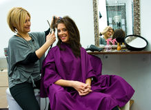 Hair stylist at work. Hair stylist work on happy woman hair in salon Stock Images