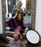 Hair stylist at work. Hair stylist work on woman hair in salon Royalty Free Stock Photo