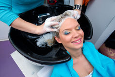 Hair stylist at work. Hair stylist washing woman hair in salon pool Royalty Free Stock Photography