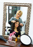 Hair stylist at work. Hair stylist work on happy woman hair in salon Stock Image