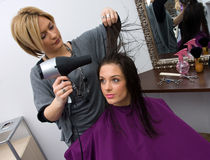 Hair stylist at work. Hair stylist work on woman hair in salon Stock Images