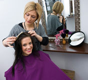 Hair stylist at work. Hair stylist work on woman hair in salon Stock Image
