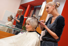 Hair stylist at work. Stylist work on woman hair in salon Royalty Free Stock Photo