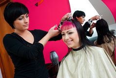 Hair stylist at work. Hair stylist working on teenage girl in salon Royalty Free Stock Images