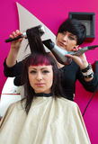 Hair stylist at work. Stylist with hair dryer working on teen girl in salon royalty free stock photography