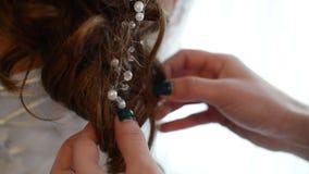 Hair stylist working on a bride`s hair