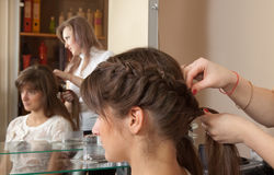 Hair stylist works on  hair in salon Stock Photo