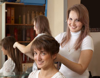 Hair stylist works on woman hair. Hair stylist works on women hair in salon Royalty Free Stock Photography