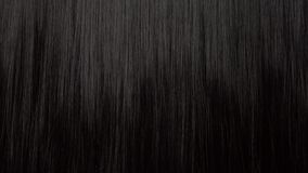 Hair texture background, no person. Black shiny hair with a comb stock video footage