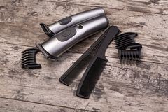 Hair trimmer with comb. On the wooden background royalty free stock image