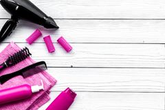 Hair washing and styling tools. Comb, shampoo, hairspray, curlers, hairdryer on white wooden background top view stock photography