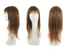 Hair wig over the mannequin head. Open wave hair wig over the white plastic mannequin head isolated over the white background, set of three foreshortenings Royalty Free Stock Image