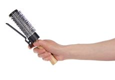 Hairbrush with a clip in hand Stock Photography
