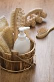 Hairbrush massager and wooden bucket Royalty Free Stock Photography