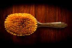 Hairbrush on wood. Vintage hairbrush on solid dark wood Stock Photos