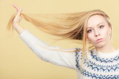 Teenage blonde girl brushing her hair with comb royalty free stock image