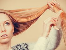Teenage blonde girl brushing her hair with comb stock photography