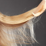 Haircare concept. Straight blonde hair with comb. Haircare concept. Closeup straight blonde hair with wooden comb Stock Photography